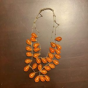 Gold colored necklace w/ tangerine dangling beads